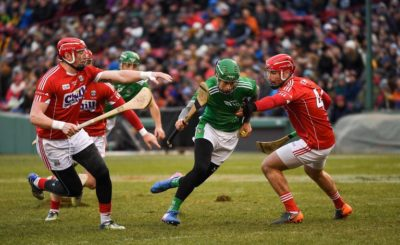 Limerick player being tackled by two Cork defenders in the Fenway Hurling Classic at Fenway Park Boston on Sunday November 18th 2018