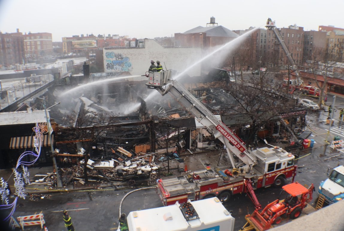 Firefighters attending the scene of a large fire on Sunnyside ,Queens New York City, which completely destroyed several businesses including Irish bar Sidetracks